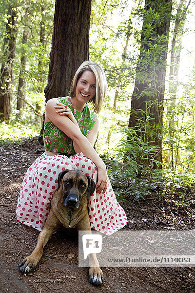 Mixed race woman and dog in forest