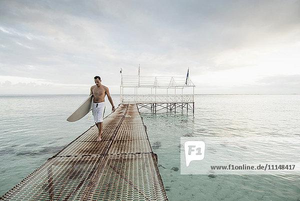 Surfer carrying surfboard on metal dock over ocean Surfer carrying surfboard on metal dock over ocean