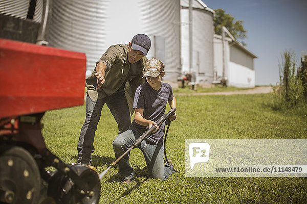 Caucasian farmer and son cleaning machinery on farm