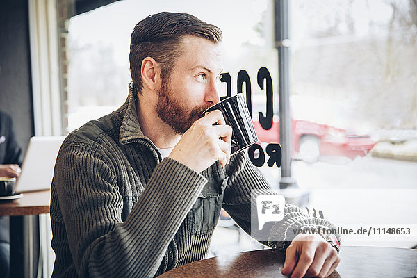 Caucasian man drinking coffee in cafe