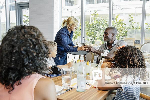 Server bringing drinks for family at restaurant