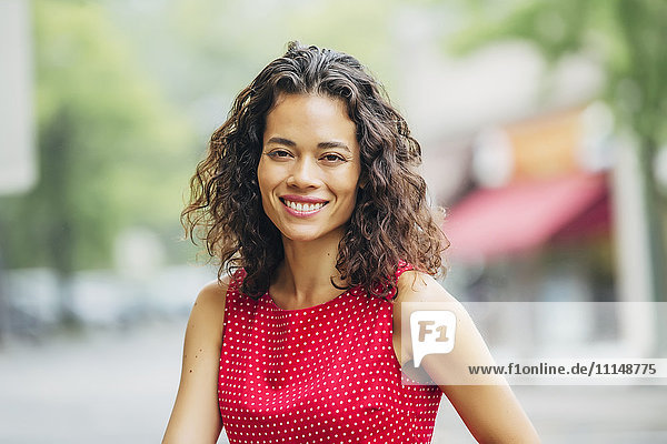 Mixed race woman smiling in city