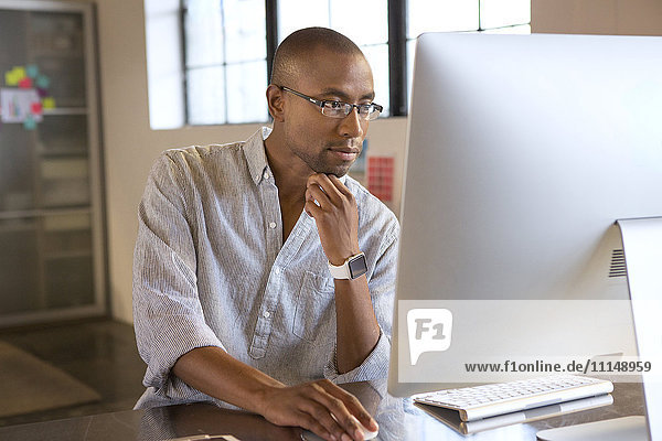 Mixed race businessman using computer in office