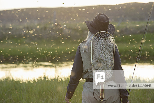 Caucasian woman wearing fishing gear in remote lake