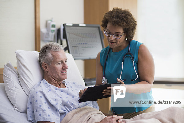 Doctor using digital tablet with patient in hotel room