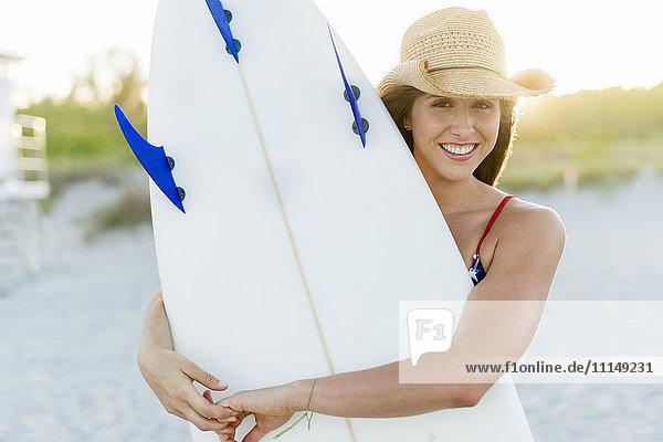 Hispanic woman carrying surfboard on beach