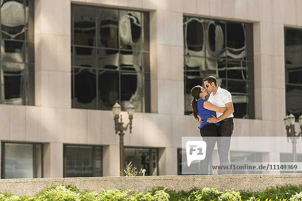 Hispanic couple kissing in city