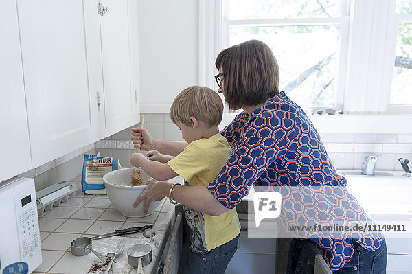 Mother and son baking in kitchen