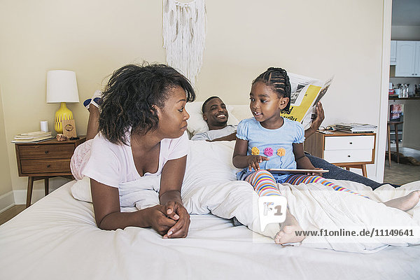 African American parents and daughter on bed