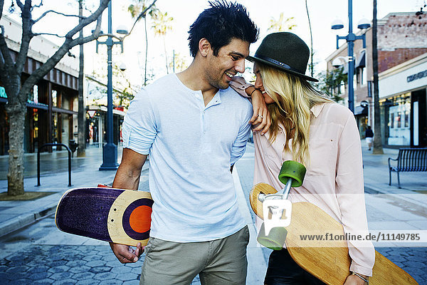 Caucasian couple carrying skateboards