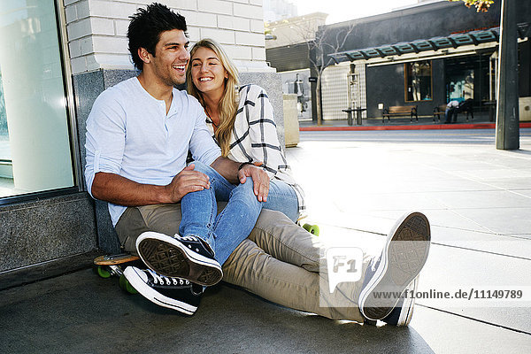 Caucasian couple sitting on sidewalk