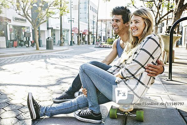 Caucasian couple sitting on skateboards
