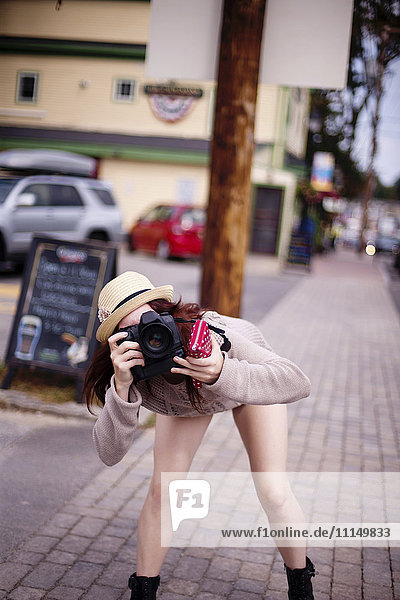 Caucasian woman photographing outdoors