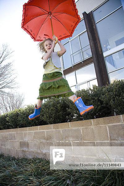 Caucasian girl jumping with umbrella