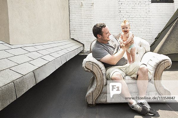 Caucasian father and baby daughter sitting in armchair outdoors