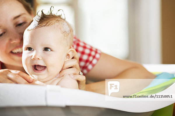 Caucasian mother bathing baby daughter