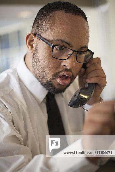 Mixed race man talking on telephone