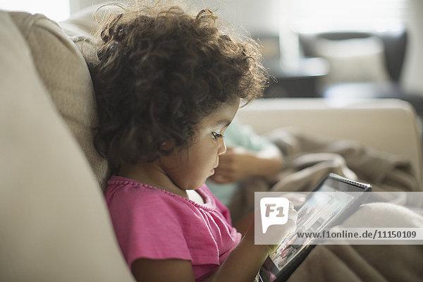 Girl using digital tablet on sofa