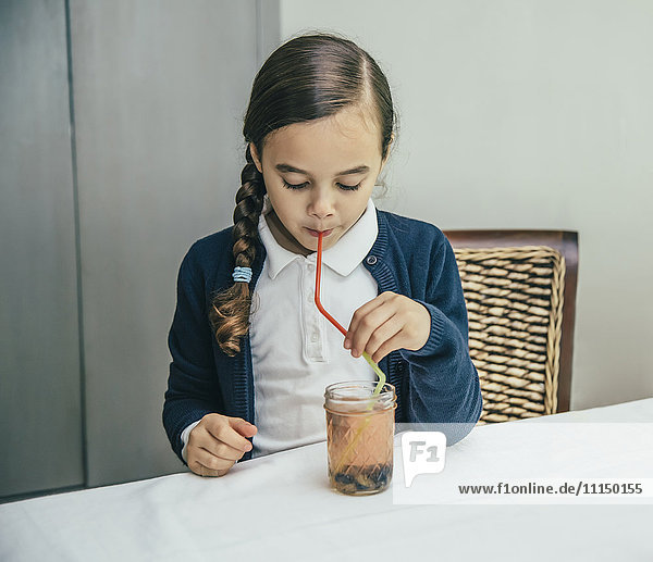 Mixed race girl drinking juice from jar through straw
