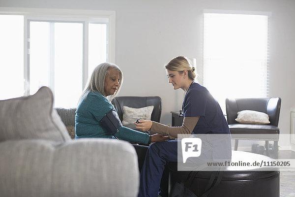 Nurse taking patient blood pressure in living room