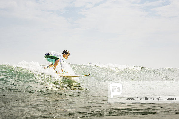 Mixed race boy surfing in waves