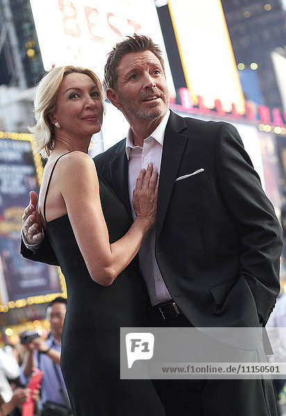 Caucasian couple hugging in Times Square  New York City  New York  United States