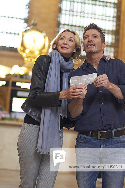 Caucasian couple reading train schedule in Grand Central Station  New York City  New York  United States