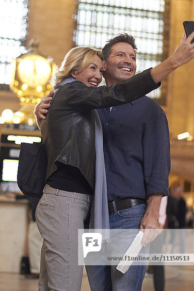 Caucasian couple taking cell phone selfie in Grand Central Station  New York City  New York  United States