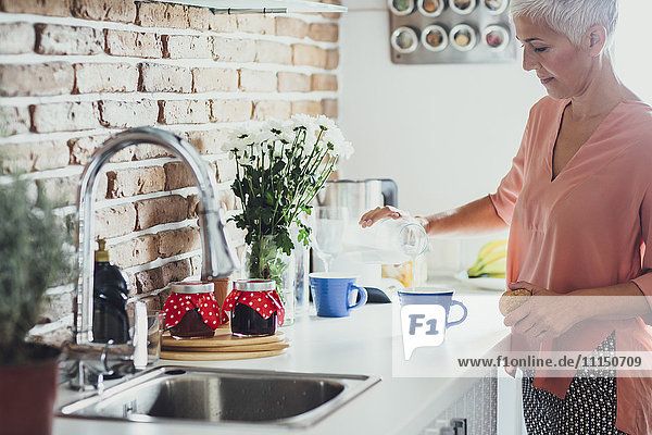 Older Caucasian woman making coffee in kitchen