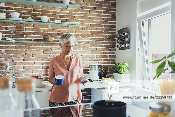 Older Caucasian woman using cell phone in kitchen