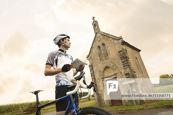 Caucasian cyclist reading map near church