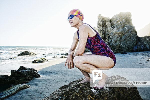 Older Caucasian woman crouching on rock on beach Older Caucasian woman crouching on rock on beach
