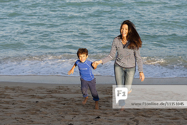 Caucasian mother and son playing on beach