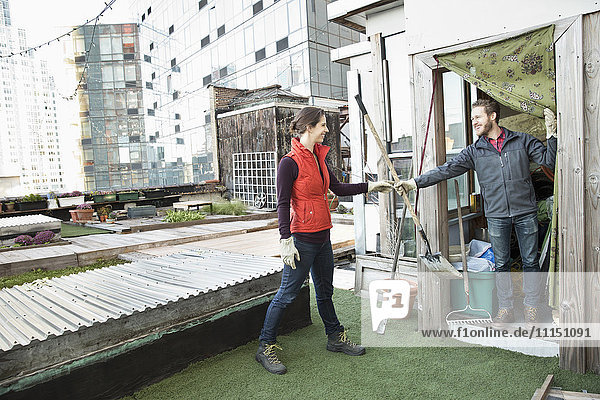 Couple holding gardening tools on urban rooftop