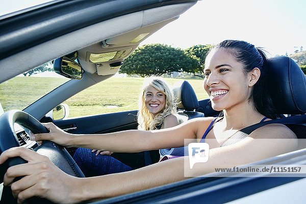 Excited women driving convertible on road trip