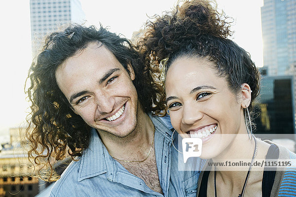Couple smiling on urban rooftop
