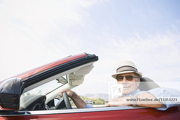 Older Caucasian man driving convertible