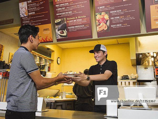Hispanic man purchasing food in cafe