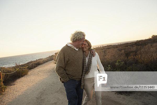 Older Caucasian couple walking on dirt path