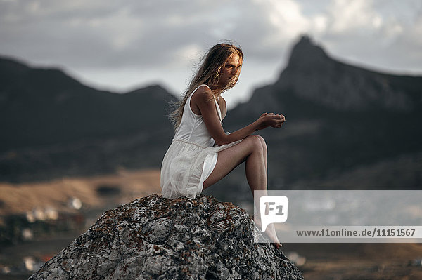 Caucasian woman sitting on remote hilltop
