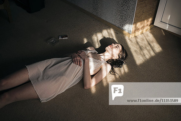 Caucasian woman laying in sun spot on floor