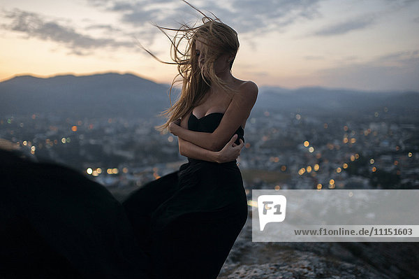 Caucasian woman on hilltop near cityscape view