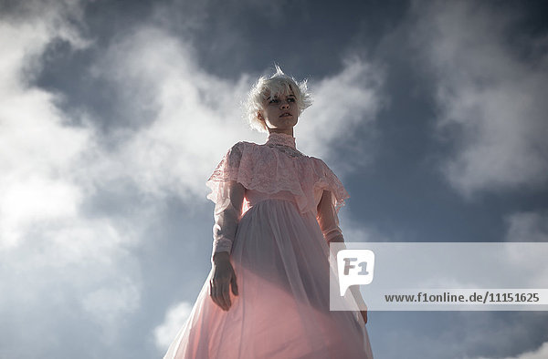 Caucasian woman walking under cloudy sky
