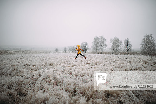 Caucasian woman leaping in snowy field
