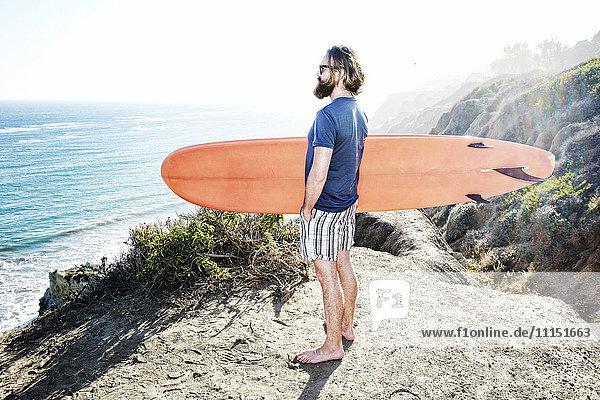 Caucasian man holding surfboard on coastal hilltop Caucasian man holding surfboard on coastal hilltop