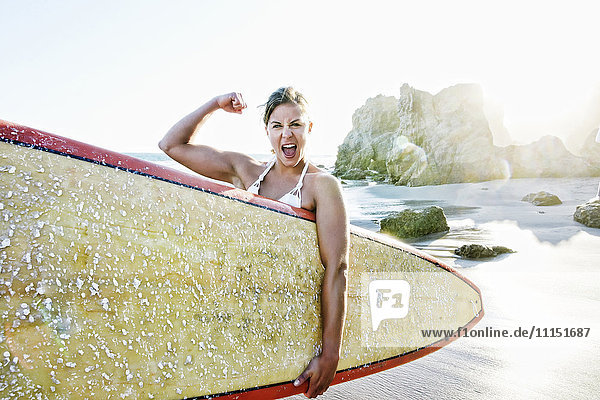 Caucasian surfer flexing muscle at beach