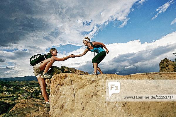 Woman helping friend climb rock formation Woman helping friend climb rock formation