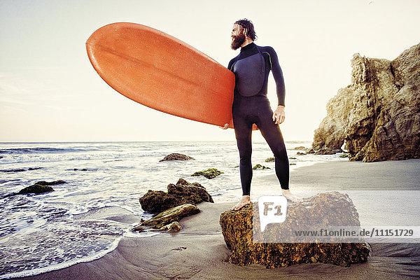 Caucasian man holding surfboard at beach Caucasian man holding surfboard at beach