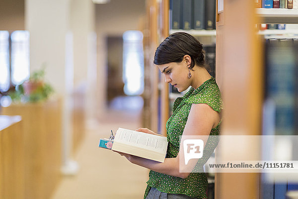 Mixed race student reading book in library
