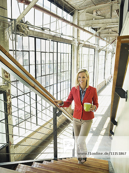 Caucasian businesswoman carrying cup of coffee on warehouse staircase